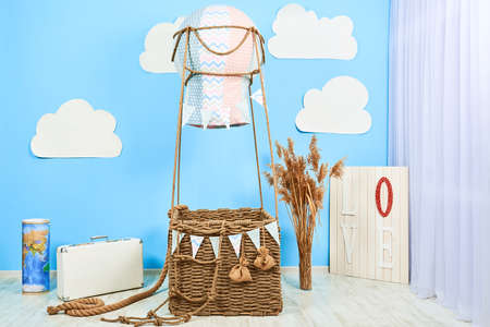 Interior room for a boy. White clouds fly toy basket of balloon. Air balloon at solid color background with copy space.