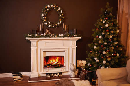 Christmas tree with beautiful balls in a cozy brown living room with a fireplase. Christmas room interior design, Xmas tree decorated by lights, candles and garland lighting indoors fireplace