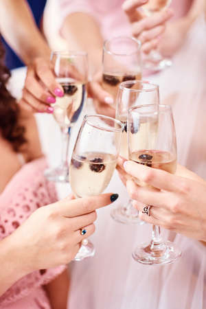 The bridesmaids are holding champagne glasses. They contain blackberries. The concept of the holiday, wedding, fun. Close-up, vertical photo
