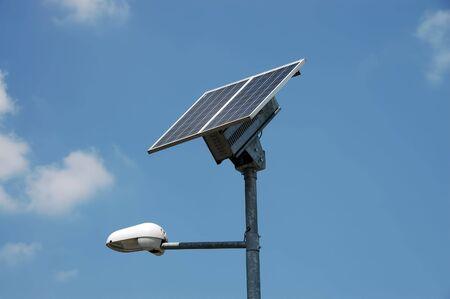 A solar powered public lamp against a blue sky.