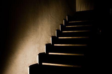 bajando escaleras: Escaleras oscuros iluminan unevely por un foco casi en la oscuridad