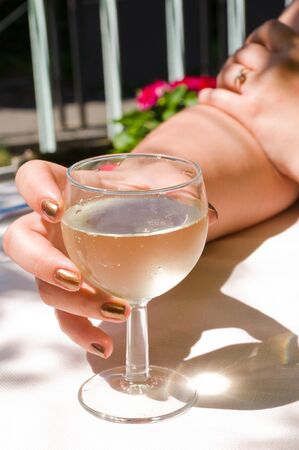 vanished: A hand holding a transparent glass of wine with vanished nails.