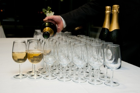 A butler serving a glass of sparkling wine in glasses in a ordered fashion over a white table photo