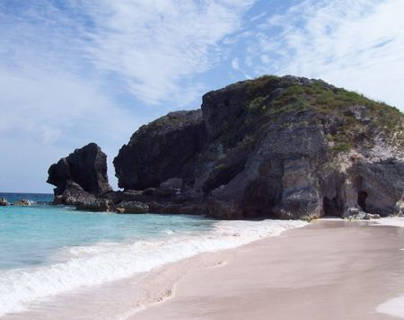 The breathtaking view in Bermuda showcases the pink sand and rocky shores.