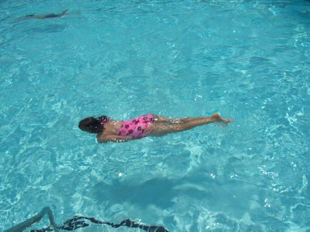 Pretty girl swimming underwater in a crystal clear pool. Stock Photo