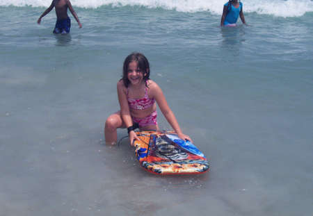Girl surfing with boogie board at beach Stock Photo