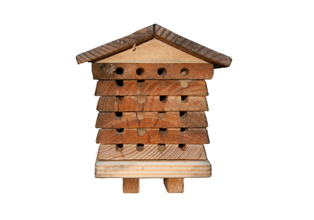 Solitary bee apiary house made of wood. Isolated bee house with round holes for entrances. Reklamní fotografie
