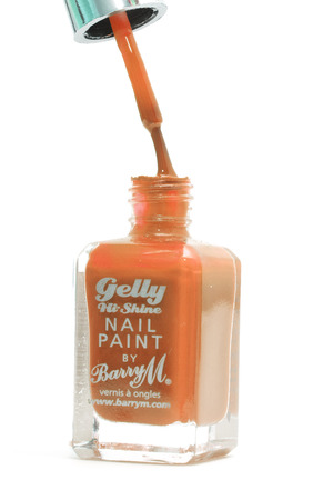 CHESHIRE, UK - February 9 2015. Orange Gelly Hi Shine Nail Polish by Barry M isolated on a white