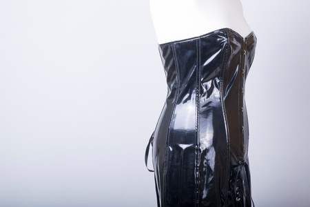Tailors Mannequin dressed in a Black PVC Corset Dress Archivio Fotografico - 107877589