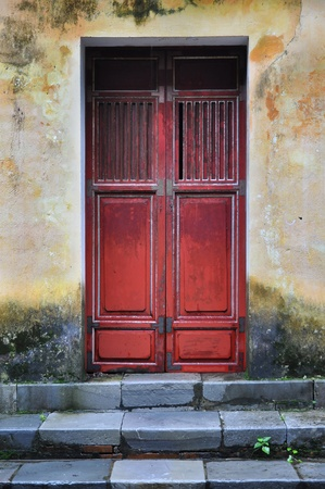 Old Vietnamese door and weathered yellow wall  Shot at Tu Duc tomb near Hue, Vietnam