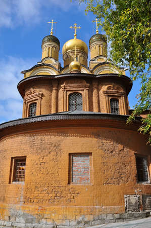 Old brick church with distinctive golden domes and crosses  Stock Photo