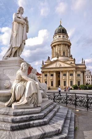 독일 시인 프리드리히 쉴러의 대리석 동상과 백그라운드에서 프랑스 교회를 보여주는 베를린, 겐 다멘 마크 트 광장에서 가장 아름다운 광장 중 하나 스톡 사진