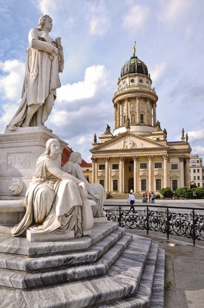 One of the most beautiful squares in Berlin, the Gendarmenmarkt, showing a marble statue of German poet Friedrich Schiller and the French Cathedral in the background