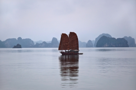 Traditional junk at Halong Bay, Vietnam, showing famous limstone karst in the background