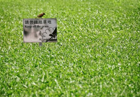 Keep of the Grass sign in English and Chinese, with sparrow perched on top, Hong Kong