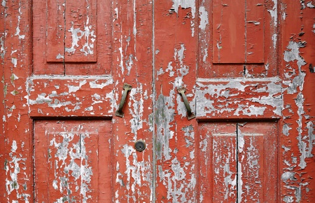 Close-up of weathered texture and peeling red paintwork of an old wooden door