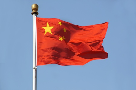 Chinese national flag on flag pole against a clear blue sky  Shot in Tiananmen Square, Beijing  Stock Photo