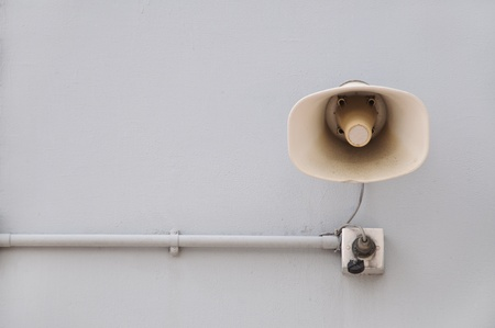 Public address system loudspeaker mounted on a white wall  Stock Photo