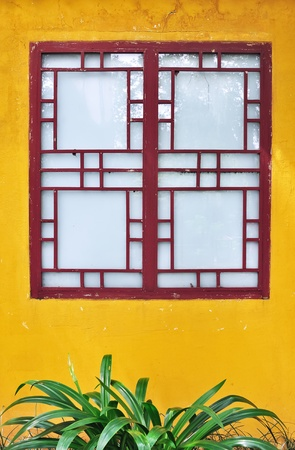 Exterior view of a traditional chinese-style wooden window set against a bright yellow painted wall  Shot in Guilin, China  Stock Photo