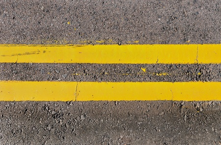 Double yellow lines running horizontally on a grey asphalt road
