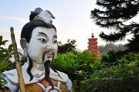 Statue at the Ten Thousand Buddhas Monastery, Hong Kong, with red pagoda in the background  One of the major cultural attractions in Hong Kong  The pagoda was even featured on the HonhgKong  100 note  Stock Photo - 13353370
