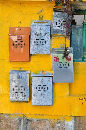 Metal Chinese mailboxes on a yellow wall, Cheung Chau, Hong Kong