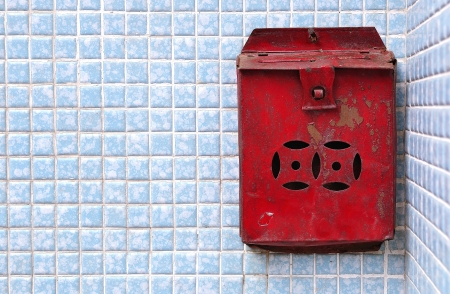 Rusty traditional red post box on a blue tiled wall, Hong Kong