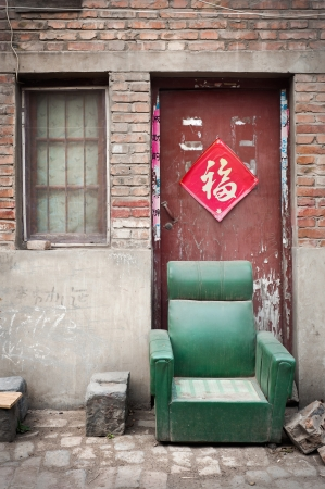 Abandoned armchair in a dusty hutong, Kaifeng, China Stock Photo