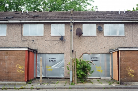 Abandoned terraced housing with metal shutters, Salford, UK