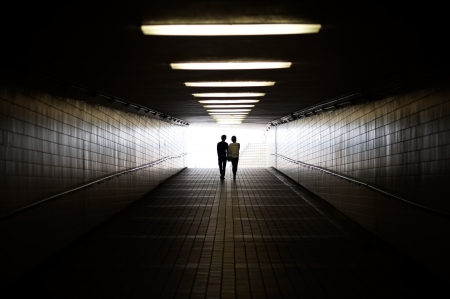 Young couple in silhouette walking towards exit of pedestrian underpass photo
