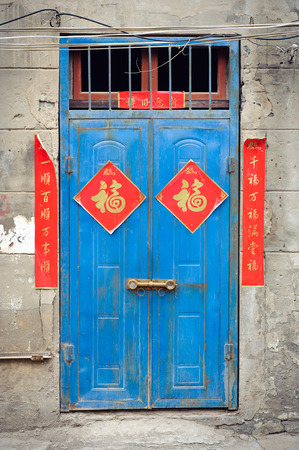 Old blue Chinese door with red good fortune posters 写真素材