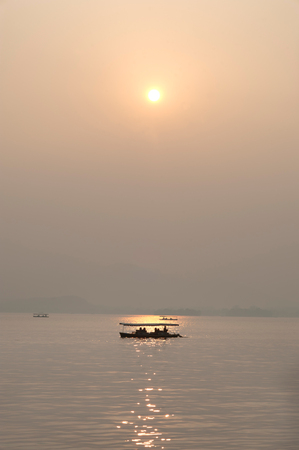 Sunset and boat silhouette, West Lake, Hangzhou, China