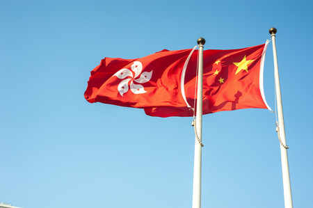 Hong Kong and China national flags flying against a blue sky