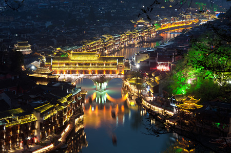 lit: Elevated view of Fenghuang ancient town lit up at night