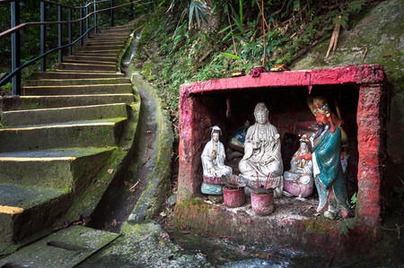 Outdoor shrine containing statues of the Goddess of Mercy and Guan Yu, Hong Kong Stock Photo