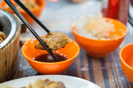 Fried spring roll held by chopticks at a Hong Kong dai pai dong