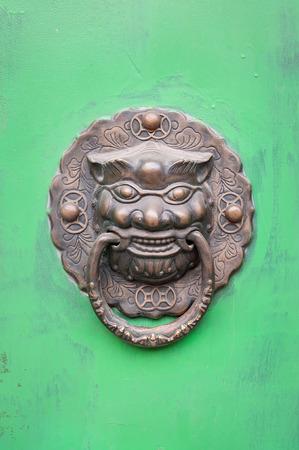 Lion-shaped door knocker on a green door in Beijing, China photo