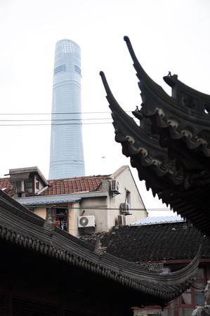 juxtaposition: Shanghai Tower rising up above the ancient rooves of Yu Garden Shanghai China Stock Photo
