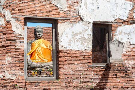 sash: Buddha statue with orange sash seen through the window of a ruined building at  Wat Worachet Tharam, Ayutthaya, Thailand