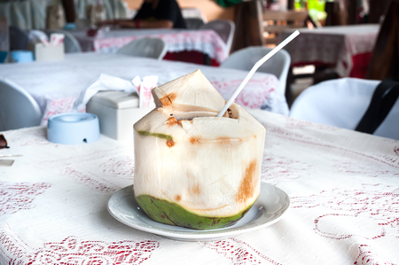 Fresh coconut with drinking straw at a Thailand restaurant