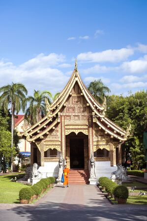 A young monk exits Wihan Lai Kham at Wat Phra Singh, Chiang Mai, Thailand