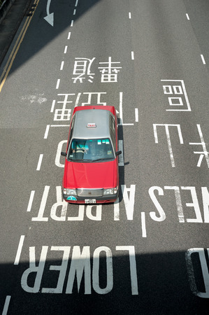 Red Hong Kong taxi seen from above in the Central district of Hong Kong Island