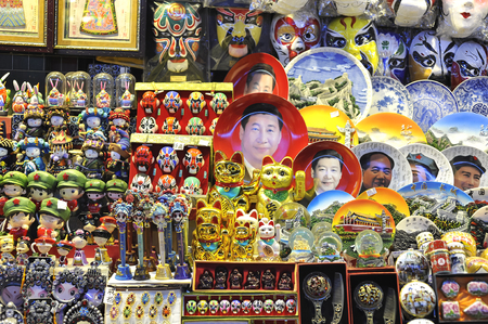 A souvenir stall at a Beijing night market selling Xi Jinping face plates and other kitsch rubbish.