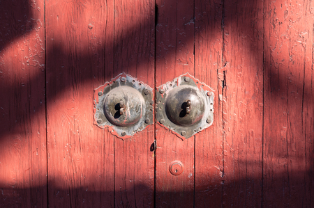 Old red wooden door with patterned shadows, Beijing, China