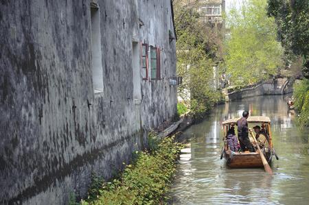 SUZHOU, CHINA - MARCH 31, 2013 - Traditional rowing boat taking tourists along the canal on Pingjianglu, Suzhou, China Editorial