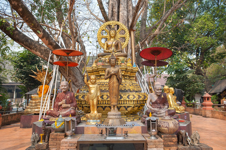Small chedi surrounded by Buddha status at Wat Jed Yod, Chiang Mai, Thailand
