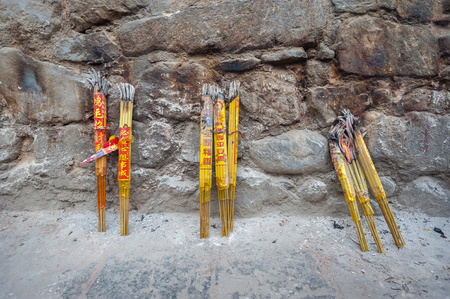Bundles of incense sticks leaning against a stone wall at a Chinese temple