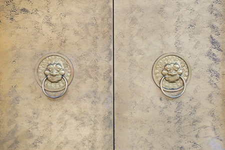 Two lion-shaped metal knockers on a Chinese door