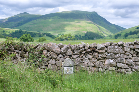 Cumbrian hills with an old-style milestone and drystone wall in the foreground, Cumbria, UK Stock fotó