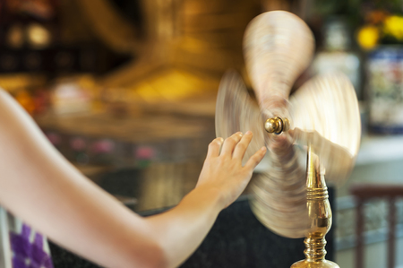 TAI WAI, HONG KONG - SEPT 15, 2013 - Worshipper at Che Kung Temple, Tai Wai, spinning a brass wheel of fortune
